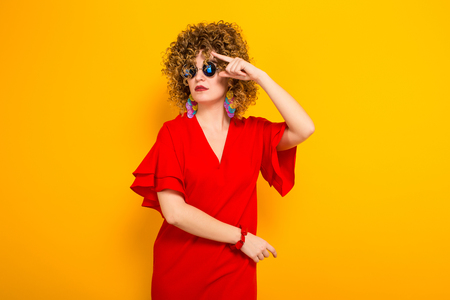 Portrait of a white woman with afrro curly hairstyle in red dress and sunglasses isolated on orange background with copyspace beauty salon advertisement concept.