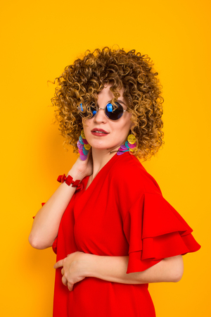 Close up portrait of a white woman with afrro curly hairstyle in red dress and sunglasses touching her hair isolated on orange background beauty salon advertisement concept.