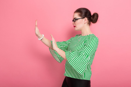 Portrait of attractive cheerful businesswoman with hair bun in striped blouse and eyeglasses showing STOP sign gesture with her palms standing aside isolated on pink background with copyspace.