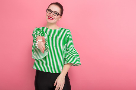 Portrait of attractive businesswoman with hair bun in striped blouse and eyeglasses giving hand for handshake isolated on pink background with copyspace getting acquainted.