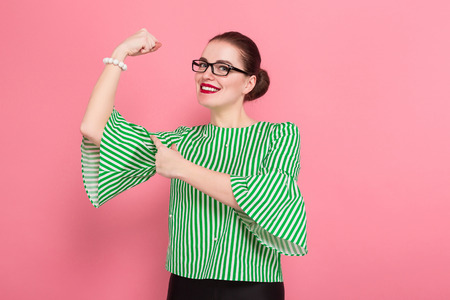 Portrait of attractive scared businesswoman with hair bun in striped blouse and eyeglasses showing her muscles isolated on pink background with copyspace. Stock Photo