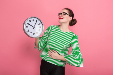 Portrait of attractive cheerful businesswoman with hair bun in striped blouse and eyeglasses showing watches isolated on pink background with copyspace punctuality being late concept.