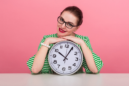 Portrait of attractive businesswoman with hair bun in striped blouse and eyeglasses showing watches sits at table isolated on pink background with copyspace punctuality being late concept.