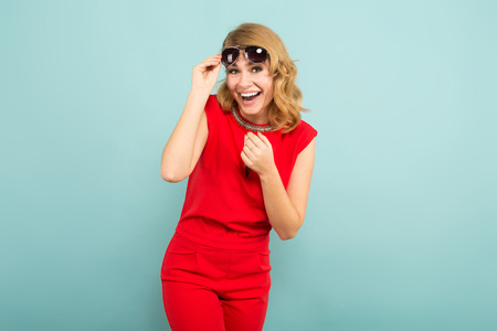 Attractive laughing woman in red costume holding her sunglasses and looking into camera isolated on blue background with copyspace invitation discount sales beauty salon concept.