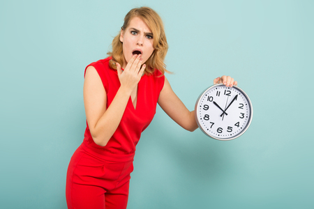 Portrait of attractive pop-eyed blonde woman in red isolated on blue background holding clocks and covering her mouth in shock time limit punctuality concept.