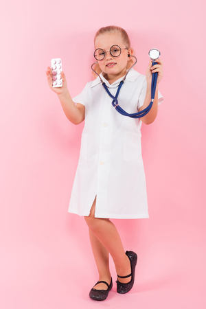 Portrait of little girl dressed like doctor in white coat and eyeglasses listening a stethoscope and holding pills isolated on pink background with copyspace pediatrics concept.