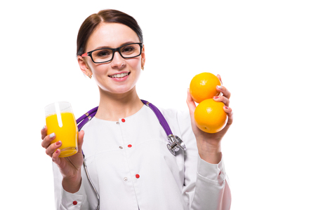 Portrait of young attractive caucasian brunette positive friendly smiling woman nutritionist standing in office with fruit mandarin orange and glass of fresh juice in her hands looking in camera in white uniform. Stock Photo