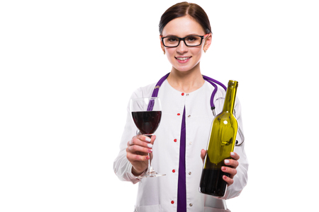 Portrait of young attractive female doctor in white coat smiling looking in camera holding bottle and glass of wine