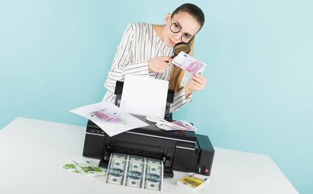 Portrait of attractive woman in striped shirt and eyeglasses isolated on blue background printing dollar and euro banknotes and checking them through magnifying glass counterfeiter greed concept.