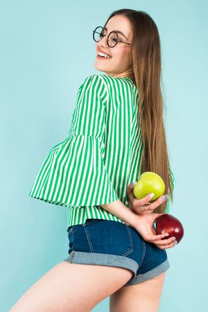 Portrait of attractive young long-haired girl in striped shirt, glasses and jeans shorts hiding red and green apples behind back isolated on blue background with copyspace healthy way of life concept.
