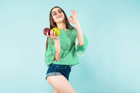Portrait of attractive long-haired girl in striped shirt, glasses and jeans shorts hold red and green apples and show OK sign isolated on blue background with copyspace healthy way of life concept.