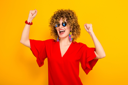 Portrait of a white woman with afrro curly hairstyle in red dress and sunglasses holding fists up in excitment isolated on orange background with copyspace advertising winning concept. Stock Photo