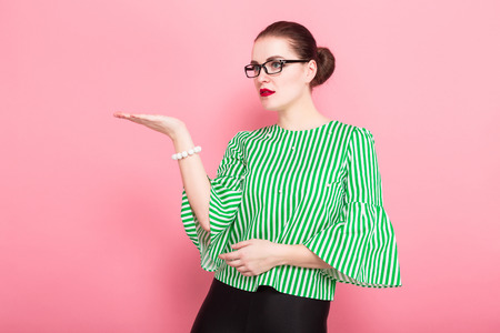 Portrait of attractive cheerful businesswoman with hair bun in striped blouse and eyeglasses presenting something on her hand isolated on pink background with copyspace. Banco de Imagens