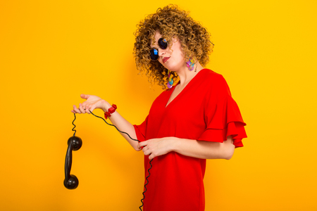 Portrait of a white displeased woman with afrro curly hairstyle in red dress and sunglasses holding wire of vintage phone isolated on orange background with copyspace.