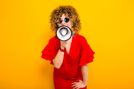Portrait of a white woman with afrro curly hairstyle in red dress and sunglasses speaking into megaphone isolated on orange background with copyspace making announcement concept. Stock Photo