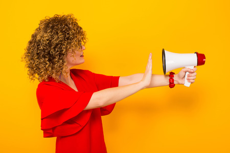White woman with afrro curly hairstyle in red dress and sunglasses holds megaphone against her face with stop sign isolated on orange background with copyspace making announcement concept.