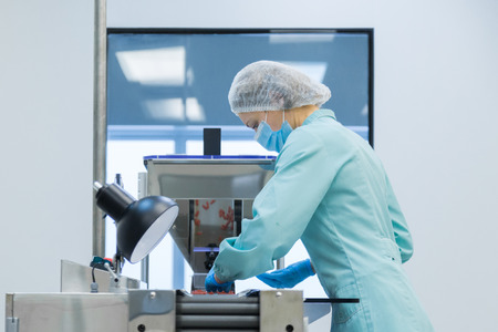 Pharmaceutical technician in sterile environment working on production of pills at pharmacy factory Archivio Fotografico