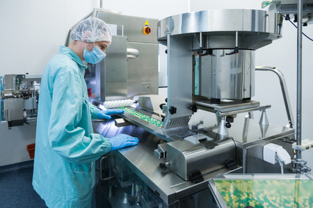 Técnico farmacéutico en ambiente estéril trabajando en la producción de píldoras en la fábrica de farmacia