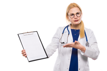 Disappointed doctor in white coat and glasses wears stethoscope and holds clip pad and shows on blank paper with palm isolated on white background wrong diagnosis or bad contract concept.