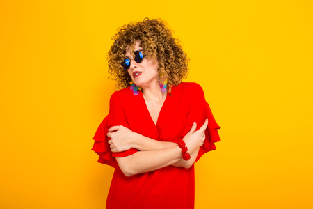Portrait of a white woman with afrro curly hairstyle in red dress and sunglasses holding herself with arms isolated on orange background with copyspace.