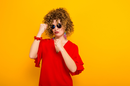 Portrait of a white woman with afrro curly hairstyle in red dress and sunglasses showing her fists ready to fight isolated on orange background with copyspace.