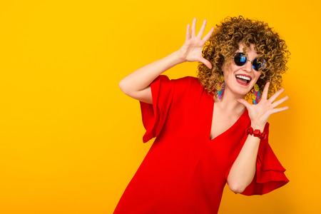 Portrait of a white cheerful woman with afrro curly hairstyle in red dress and sunglasses with palms spread isolated on orange background with copyspace advertising concept.