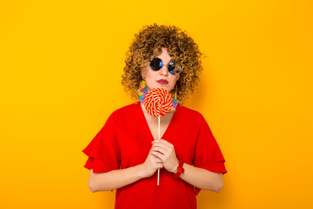 Portrait of a white woman with afrro curly hairstyle in red dress and sunglasses holding colorful lollipop isolated on orange background with copyspace. Stock Photo