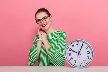 Portrait of attractive cheerful businesswoman with hair bun in striped blouse and eyeglasses showing watches sits at table isolated on pink background with copyspace punctuality being late concept. Stock Photo