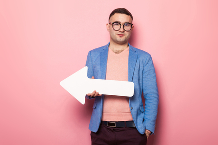 Portrait of handsome businessman in pink jumper, blue jacket and glasses holds blank paper speech arrow pointer with empty space for text directing aside isolated on pink background.