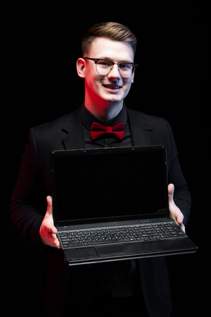 Young caucasian elegant smart business man in black suit standing in office looking in camera smiling offering laptop