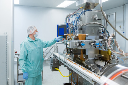 Pharmaceutical technician in sterile environment working with equipment at pharmacy industry Stock Photo