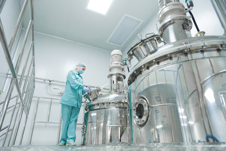 Pharmaceutical technician in sterile environment at pharmacy industry Stock Photo