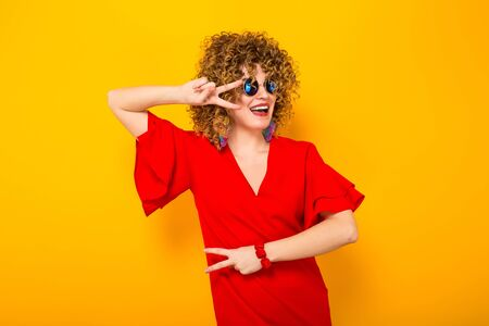 Portrait of a white woman with afrro curly hairstyle in red dress and sunglasses holding two fingers near her eyes isolated on orange background with copyspace beauty salon advertising concept.