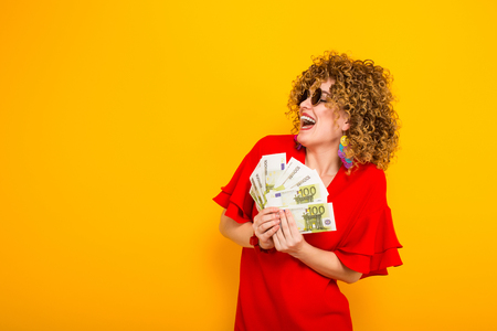 Portrait of a white happy woman with afrro hairstyle in red dress and sunglasses holding fan of euro bills isolated on orange background with copyspace winning in lottery money withdraw concept.