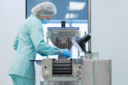 Pharmaceutical technician in sterile environment working on production of pills at pharmacy factory Stock Photo
