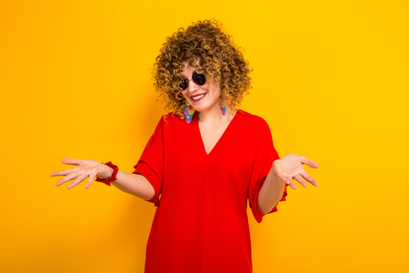Portrait of a white woman with afrro curly hairstyle in red dress and sunglasses standing with arms spread does not know what to do isolated on orange background with copyspace. Stock Photo