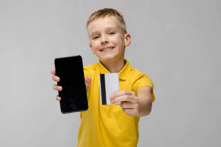 Handsome small adorable confident happy friendly boy standing in studio looking in camera offering phone and credit card advertising phone Stockfoto