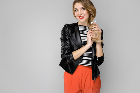 Portrait of beautiful caucasian friendly positive funny woman standing in studio looking in camera with red lips in bright clothes