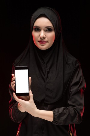 Attractive confident serious muslim arabian woman dressed in black hijab standing in studio looking in camera showing phone as business concept Stock Photo