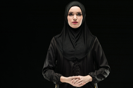 Attractive muslim arabian woman dressed in black hijab standing in studio looking in camera confident friendly serious with hand on hand