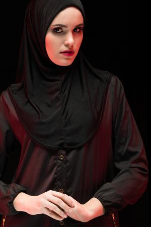 Attractive confident serious muslim arabian woman dressed in black hijab standing in studio looking in camera