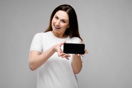 Half-length portrait of happy young brunette caucasian girl in white t-shirt on gray background excited showing mobile phone in her hands Banco de Imagens