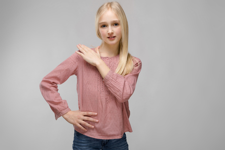 Portrait of beautiful teenage girl with blonde hair wearing pink blouse holding her hand on shoulder isolated on grey background fashion advertising concept. Stock Photo