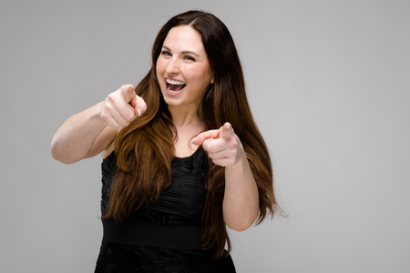 Portrait of smiling plus size model with long hair wearing black dress pointing with fingers at camera isolated on grey background with copyspace fashion advertising or beauty salon body positive concept.