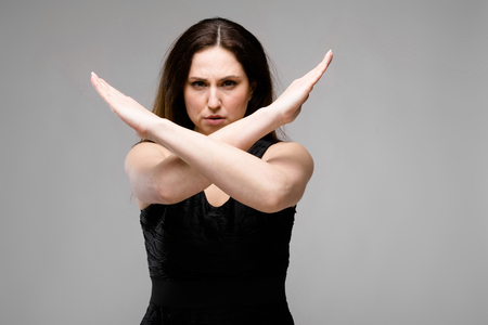 Portrait of plus size model with long hair wearing black dress showing STOP sign with her arms crossed isolated on grey background with copyspace.