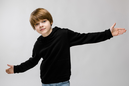 Portrait of cute little boy wearing black hoody and holding hands spread doesnt know what to do isolated on grey background with copyspace childrens fashion concept. Stock Photo