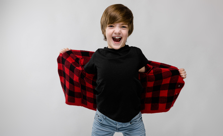 Portrait of cheerful little boy holding his checkered jacket spread and screaming at camera isolated on grey background with copyspace childrens fashion concept.