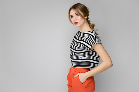 Portrait of beautiful woman with pony tail wearing striped top and pants holding hands in pockets isolated on grey background with copyspace fashion advertising or beauty salon concept. Stock Photo