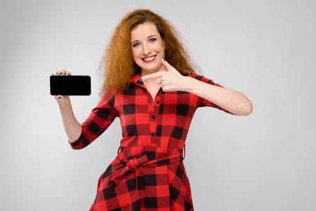 Portrait of attractive woman in checkered dress pointing at mobile phone presenting it isolated on grey background with copyspace digital advertising concept.