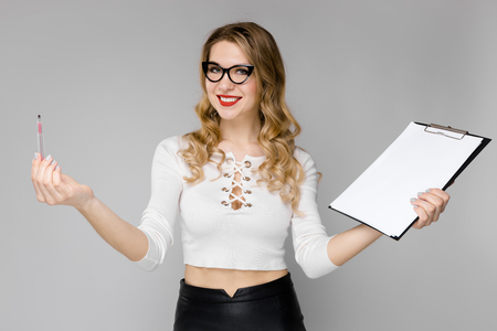 Portrait of attractive curly-haired businesswoman in white top and eyeglasses isolated on grey backgroung holding blank paper list clipped to pad and pencil coming up with good idea concept.